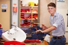 Studenten, welche die Klempnerarbeit arbeitet an der Bank studieren Stockfotos