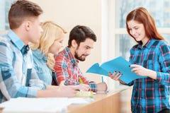 Studentenarbeit mit Testbuch lizenzfreie stockbilder