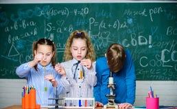 Studentenbiologieexperimente mit Mikroskop im Labor Kleine leere Flaschen Kleinkinder, die Chemie im Schullabor lernen lizenzfreie stockfotos