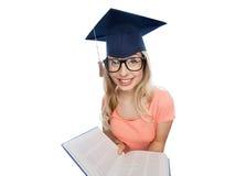 Studentenfrau in der Doktorhut mit Enzyklopädie Stockbilder