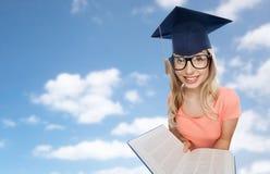 Studentenfrau in der Doktorhut mit Enzyklopädie Lizenzfreie Stockfotos