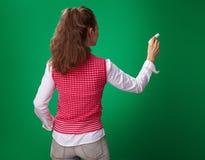 Studentenfrauenschreiben mit Stück Kreide auf grünem Hintergrund Stockfotos