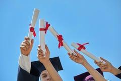 Studentengediplomeerden met hoeden en diploma's Royalty-vrije Stock Foto's
