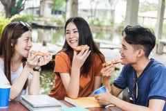 Studentengruppefrau und Fleisch fressende Pizza zusammen Stockbilder