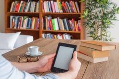 Studentenhände, die zu Hause einen ebook Leser halten lizenzfreie stockfotos