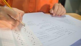 Studentenhanden die examens nemen, schrijvend onderzoeksruimte met holdi royalty-vrije stock afbeeldingen