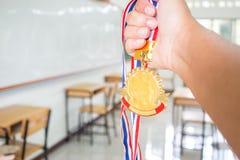 Studentenhanden opgeheven holding twee gouden medailles met Thais lint a Stock Fotografie