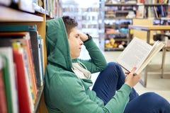 Studentenjongen of jonge mensenlezingsboek in bibliotheek Stock Foto