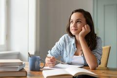 Studentenjugendliche, die zu Hause das Träumen studiert Stockbilder