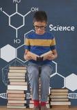 Studentenjunge auf einer Tabellenlesung gegen blaue Tafel mit Wissenschaftstext und -graphiken stock abbildung