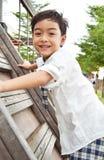 Studentenjunge klettern oben am Spielplatz stockfotografie