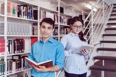Studentenlesebuch zusammen in der Bibliothek Lizenzfreie Stockfotos
