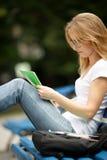 Studentenlesung konferiert beim Sitzen auf Parkbank stockbild