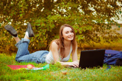 Studentenmädchen auf Gras mit einem Computer Stockfoto