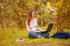 Studentenmädchen auf Gras mit einem Computer Lizenzfreies Stockbild