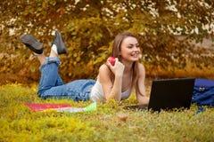 Studentenmädchen auf Gras mit einem Computer Lizenzfreies Stockfoto