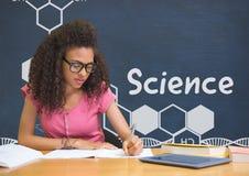 Studentenmädchen bei Tisch, das gegen blaue Tafel mit Wissenschaftstext und -graphiken liest Stockfotos