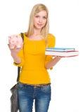 Studentenmädchen, das Bücher und piggy Querneigung zeigt Lizenzfreies Stockfoto