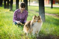 Studentenmädchen, das in der Natur mit Hund lernt Lizenzfreie Stockbilder