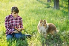 Studentenmädchen, das in der Natur mit Hund lernt Lizenzfreie Stockfotos
