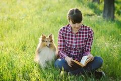 Studentenmädchen, das in der Natur mit Hund lernt Stockfoto