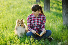 Studentenmädchen, das in der Natur mit Hund lernt Lizenzfreies Stockfoto