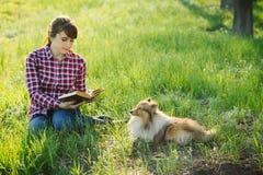 Studentenmädchen, das in der Natur mit Hund lernt Lizenzfreie Stockfotografie