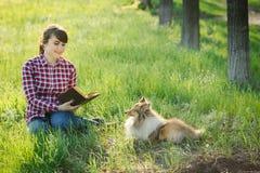 Studentenmädchen, das in der Natur mit Hund lernt Stockfotos