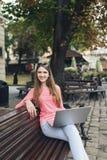 Studentenmädchen, das mit einem Laptop in der alten Stadt arbeitet Lizenzfreie Stockbilder
