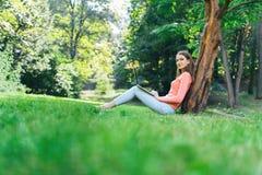 Studentenmädchen, das mit einem Laptop in einem grünen Park arbeitet Stockbild