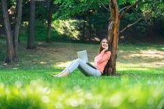 Studentenmädchen, das mit einem Laptop in einem grünen Park arbeitet Lizenzfreies Stockbild