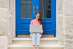 Studentenmädchen, das mit einem Laptop vor blauen Türen arbeitet Stockbilder
