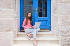 Studentenmädchen, das mit einem Laptop vor blauen Türen arbeitet Stockbild