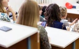 Studentenmädchen, das am Vortrag sitzt lizenzfreie stockbilder