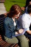 Studentenmädchen, das zum Notizbuch am Campus schreibt Lizenzfreie Stockfotografie