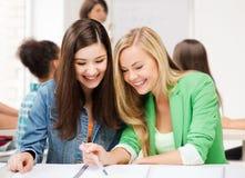 Studentenmädchen, die in der Schule auf Notizbuch zeigen Stockfotografie