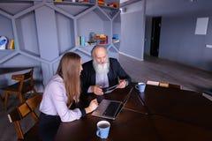 Studentenmädchen erklärt, wie man Laptop zu Professor, geben advic benutzt Lizenzfreie Stockfotografie