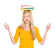 Studentenmädchen mit Büchern auf dem Hauptmeditieren Lizenzfreies Stockfoto