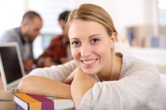 Studentenmädchen mit Buch im Klassenzimmer, das Pause macht Lizenzfreies Stockfoto