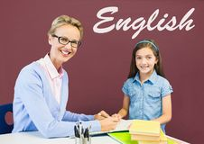 Studentenmädchen und -lehrer bei Tisch gegen rote Tafel mit englischem Text Stockfotos