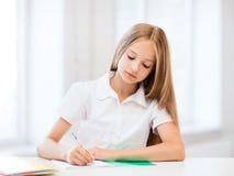 Studentenmädchen, das an der Schule studiert Lizenzfreie Stockfotos