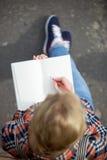 Studentenmeisje die nota's in een voorbeeldenboek maken stock afbeelding