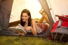 Studentenmeisje in een tent en holding een boek stock afbeelding