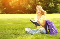 Studentenmeisje met boek en rugzak in park Royalty-vrije Stock Afbeelding