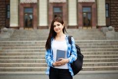 Studentenmeisje met boeken en rugzak die zich dichtbij universitaire bu bevinden royalty-vrije stock fotografie