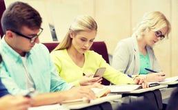 Studentenmeisje met smartphones bij lezing stock foto