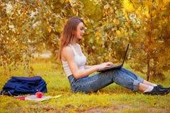 Studentenmeisje op gras met een computer Stock Fotografie