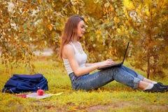 Studentenmeisje op gras met een computer Stock Afbeeldingen