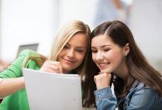 Studentenmeisjes die op notitieboekje op school richten Stock Afbeeldingen