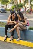 Studentenmeisjes met smartphones Havana Stock Fotografie